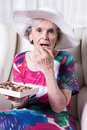 Active female senior earing chocolate candy Royalty Free Stock Photos
