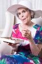 Active female senior earing chocolate candy Stock Image