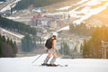 Active female skier skiing on the snowy slope of the mountain, wearing ski equipment, backpack, helmet Royalty Free Stock Photo