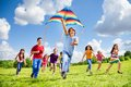 Active games for many kids happy large group of boys and girls with kite and laughing boy running on the foreground Stock Photo