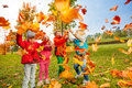 Active group of children play with flying leaves Royalty Free Stock Photo