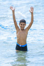 Active happy boy playing in water blue sea with arms up Stock Photos