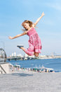 Active kid girl gymnast jumping or dancing on the street. Young girl acrobat. The girl is engaged in gymnastics. Royalty Free Stock Photo
