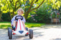 Active little boy driving pedal car in summer garden Royalty Free Stock Photo