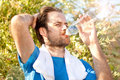 Active man drinking water after outdoor workout forty years old caucasian and having a rest during sunny summer day Royalty Free Stock Photography