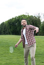 Active man playing badminton game in park, summertime concept Royalty Free Stock Photo