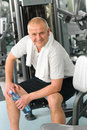 Active man relax sitting by fitness machine Stock Image