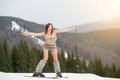 Active naked female skier having fun on the snowy slope of the mountain, wearing ski equipment Royalty Free Stock Photo