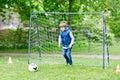 Active school kid boy playing soccer and kicking ball.