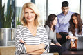 Active senior business woman portrait of women sitting at meeting while people working background Stock Image