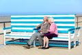 Active senior couple relaxing at the sea happy on beach sitting together on bench retirement concept Stock Photography