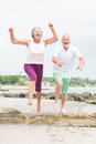Active senior couple and sporty at the beach Stock Photos