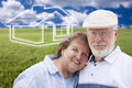 Active senior couple standing in grass field with ghosted house behind loving on the horizon Stock Image