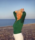 Active senior female on the beach relaxing happy elder woman looking relaxed with her hands her head Stock Photo