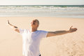 Active senior man with arms outstretched practicing yoga at beach Royalty Free Stock Photo