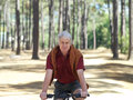 Active senior man cycling through woodland smiling front view portrait Stock Images