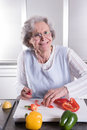 Active senior preparing paprika in kitchen Stock Images