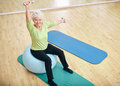 Active senior woman at gym exercising with weights sitting on a pilates ball and lifting dumbbells looking camera old caucasian Stock Photo
