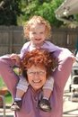 Active senior woman holds girl on her shoulders Royalty Free Stock Image