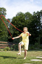Active senior woman is jumping rope in the garden Royalty Free Stock Image