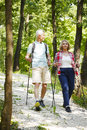 Active seniors full length portrait of senior couple enjoying a nordic walk in the forest while old men and elderly women talking Stock Photography