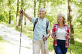 Active seniors portrait of senior couple enjoying a nordic walk elderly women and men walking on the forest and smiling Stock Photos