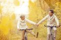 Active seniors riding bike in autumn nature they relax outdoor Stock Photo