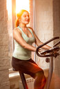 Active slim woman riding exercise bike at gym portrait of Royalty Free Stock Image