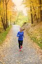 Active and sporty woman runner in autumn nature is exercising colorful Royalty Free Stock Images