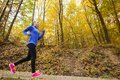 Active and sporty woman runner in autumn nature is exercising colorful Stock Photo