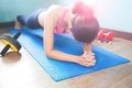 Active woman doing plank on blue yoga mat with fitness equipments, Working out Royalty Free Stock Photo