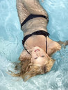 Active young blonde woman in a blue pool an image of Stock Image