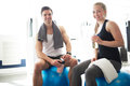 Active young couple in the gym smiling at camera relaxing on exercise ball after workout and Stock Image