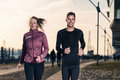 Active young couple jogging in an urban street side by side during their daily workout a health and fitness concept Royalty Free Stock Photography