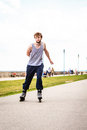 Active young man rollerskating outdoor in training suit guy riding enjoying sport Stock Photo