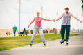 Active young people friends rollerskating outdoor in training suit woman and men couple holding hands riding enjoying sport Stock Photography