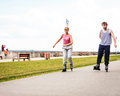 Active young people friends rollerskating outdoor in training suit woman and men riding enjoying sport Royalty Free Stock Image