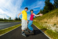 Active young people rollerblading skateboarding girl and boy roller skating Stock Photography