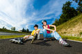 Active young people rollerblading skateboarding girl and boy roller skating Stock Photos