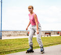 Active young woman rollerskating outdoor in training suit girl riding enjoying sport Stock Photo