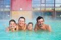 Activities on the pool portrait of happy family of four relaxing in termal swimming Royalty Free Stock Images