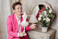 Actor sits holding stylized statuette at table in pink suit with mirror and bunch of white roses Royalty Free Stock Photo