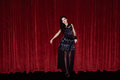 The actress appears on stage in a black dress front of scenes Royalty Free Stock Photography