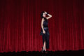 The actress appears on stage in a black dress front of scenes Royalty Free Stock Image