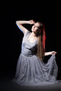 Actress in a grey dress on a dark stage Royalty Free Stock Photo
