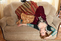 Actress in medieval dress lying upside down on sofa arms outstretched Royalty Free Stock Photo