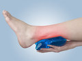 Acute pain in ankle woman holding hand to spot of ankle aches a Royalty Free Stock Image
