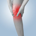 Acute pain in a knee female holding hand to spot of knee aches man male concept photo with color enhanced blue skin with read Stock Photography