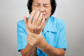 Acute pain in a senior woman wrist on grey background Royalty Free Stock Images