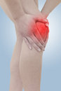 Acute pain in a woman  knee. Female holding hand to spot of knee Royalty Free Stock Image